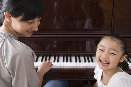 Foto de Mother playing the piano for her daughter - Imagen libre de derechos