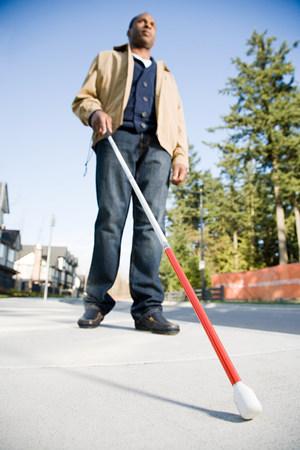 Photo pour Blind man using a walking stick - image libre de droit
