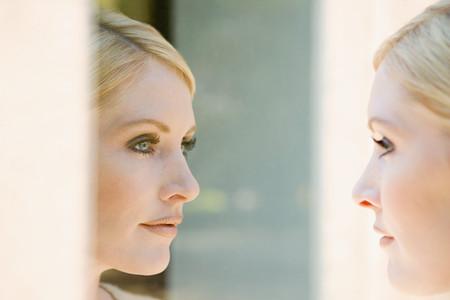 Photo pour Woman looking at her reflection - image libre de droit
