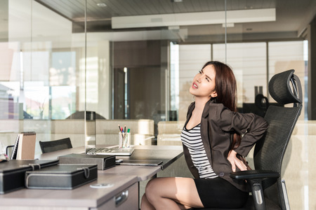 Photo for Young businesswoman having back pain while sitting at office desk - Royalty Free Image