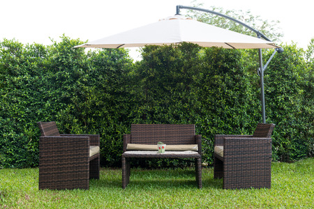 Foto de Set of rattan garden furniture under a big garden umbrella - Imagen libre de derechos