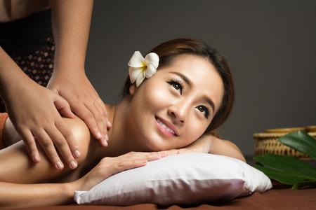 Photo pour Asian woman getting thai herbal compress massage in spa. - image libre de droit