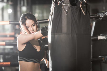 Foto de Beautiful Female Punching A Bag With Boxing Gloves at the gym. concept about sport, fitness, martial arts and people - Imagen libre de derechos