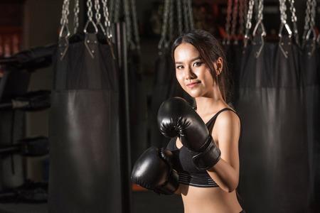 Foto de Boxer woman. Boxing fitness woman smiling happy wearing black boxing gloves. Portrait of sporty fit Asian model of boxing gym - Imagen libre de derechos
