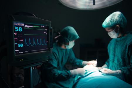 Foto de Surgeons team working with Monitoring of patient in surgical operating room. selective focus on Monitor - Imagen libre de derechos