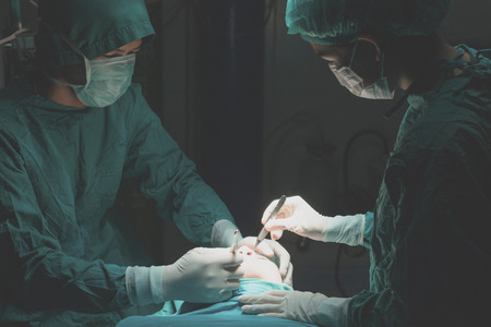 Foto de Plastic surgery wrinkle reduction , asian man during surgery using a scalpel , Plastic surgery. - Imagen libre de derechos