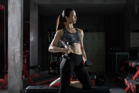 Photo for  Asian fitness girl with perfect shape body workout lifting a dumbbell in the gym,Fitness woman - Royalty Free Image