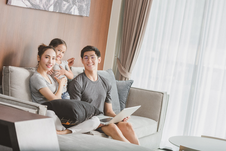 Photo pour Happy parents with daughter using laptop in living room - image libre de droit
