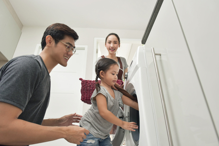 Foto de Happy Family loading clothes into washing machine in home - Imagen libre de derechos