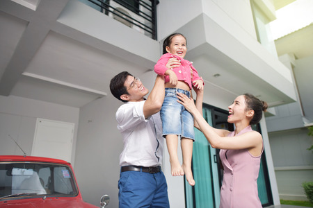 Photo for Happy parents with daughter in front of house - Royalty Free Image