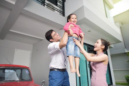Photo pour Happy parents with daughter in front of house - image libre de droit