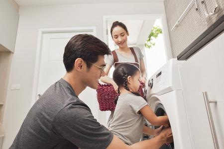 Foto de Happy Family loading clothes into washing machine in home - Imagen libre de derechos