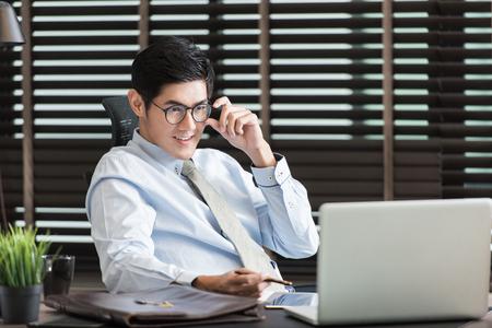 Foto de Asian businessman using his smartphone,computer in his office - Imagen libre de derechos
