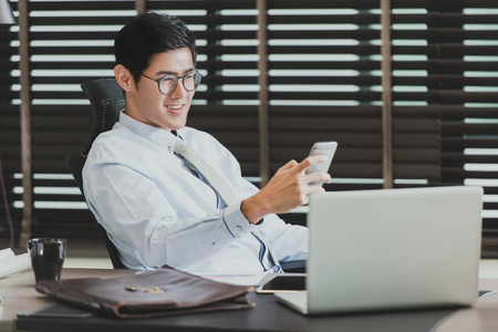Photo for Asian businessman using his smartphone,computer in his office - Royalty Free Image