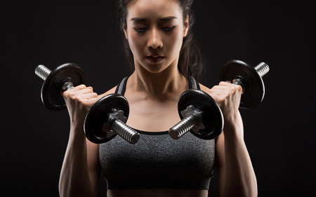 Foto de Beautiful girl exercising squatting with dumbbells on black. - Imagen libre de derechos