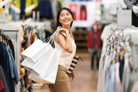 Foto de young happy woman with shopping bags in the luxury clothing store. - Imagen libre de derechos