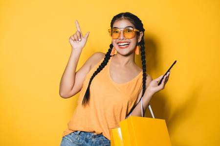 Photo pour Beautiful young woman with shopping bags using her smart phone on yellow background.Shopaholic shopping Fashion. - image libre de droit