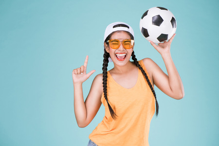 Photo pour Cute woman fan of football championship. Fit girl holding ball over Blue background. - image libre de droit