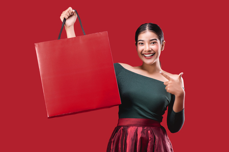 Foto für portrait of happy young cute woman posing with shopping bags over Red background. - Lizenzfreies Bild