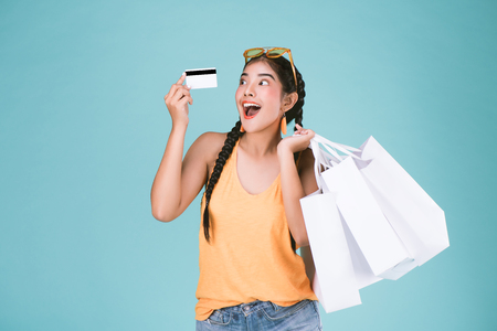 Foto de portrait of cheerful young brunette woman holding credit card and shopping bags over Blue background. - Imagen libre de derechos