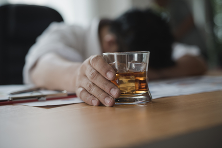 Foto de Stressed asian businessman holding a glass of whiskey he sleeping and Data Charts,business document at office desk.  alcohol addiction - drunk businessman concept - Imagen libre de derechos