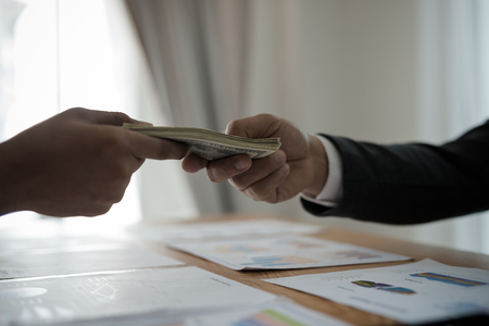 Photo for Men's hands, sending money to business travelers. Corruption and bribery concept - Royalty Free Image