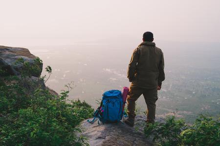 Foto de Traveler successful young man standing on top of Mountain and waiting for sunrise. - Imagen libre de derechos