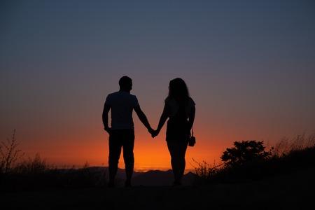 Foto de Young couple enjoying sunset in the mountains an amorous couple at sundown. - Imagen libre de derechos