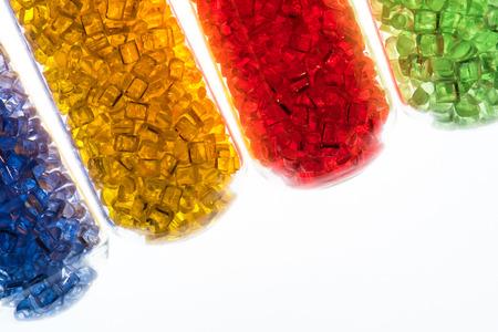 Photo pour transparent dyed plastic granulates in test tubes - image libre de droit