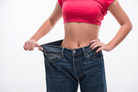 Close-up of slim waist of young woman in big jeans showing successful weight loss, isolated on white background, diet concept