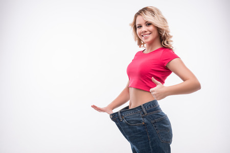 Foto de Full-length portrait of attractive slim young smiling woman in big jeans showing successful weight loss with her thumb up, isolated on white background - Imagen libre de derechos