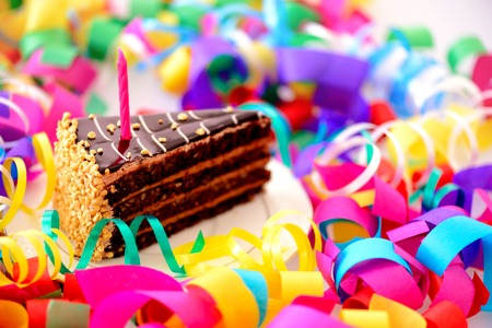 Foto de Birthday cake. Closeup top view of a piece of chocolate cake with a birthday candle decorated with confetti isolated in white background - Imagen libre de derechos