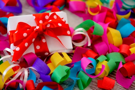 Celebrating a special day. Top view image of multicolored confetti as a frame for a gift box with red ribbon placed on wooden table