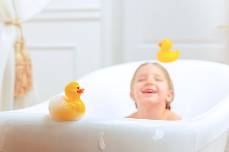 Photo for Bath time is fun. Selective focus image of a cute little girl taking a bath and playing with rubber ducks while sitting in a luxurious bathtub - Royalty Free Image