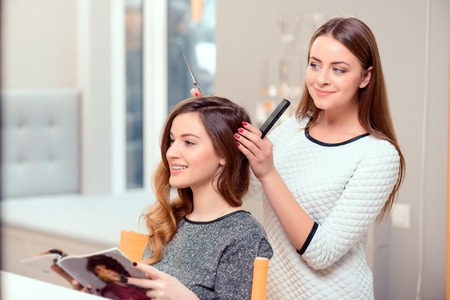 Going for a change of style. Young beautiful woman discussing hairstyling with her hairdresser holding a comb and scissors while sitting in the hairdressing salon