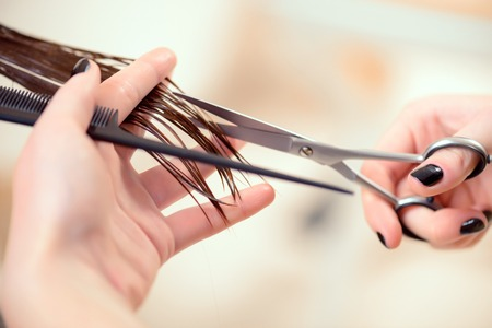 Photo pour Getting rid of those split ends. Cropped shot of a female hairdresser cutting clients hair with scissors at beauty salon - image libre de droit
