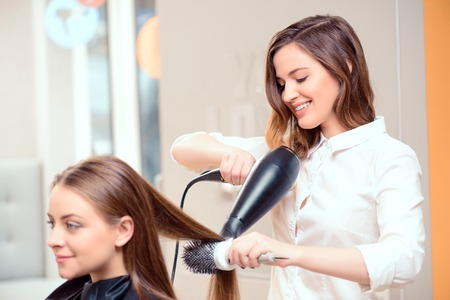 Foto de Stylish by professionals you can trust.  Mirror reflection of a young beautiful hairdresser doing her clients hair with a hair drier on the background of the hairdressing salon - Imagen libre de derechos