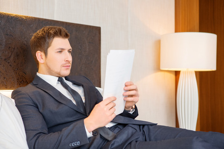 He likes business trips. Confident young businessman in suit and tie reading documents while sitting on the bed in luxury hotel room