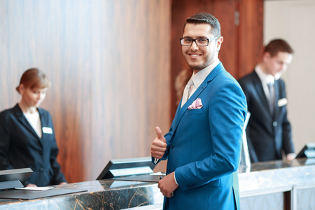 Foto de Best hotel service. Good-looking businessman in classical blue suit showing his thumb up reaches the reception desk with two receptionists on the background - Imagen libre de derechos
