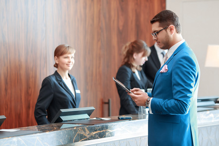 Photo for Looking for check-in information. Young handsome businessman in classical blue suit looks at his tablet device standing just in front of the hotel reception desk where young receptionists welcomes him with  a smile - Royalty Free Image