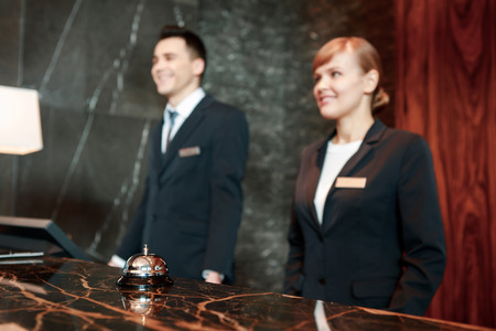 Photo for Can I help you. Selective focus on hotel service bell put with female and male receptionists in uniform standing behind the counter in blurry - Royalty Free Image