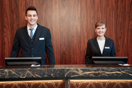 Photo pour Welcome to the hotel. Male and female receptionists standing at the front desk with wooden background welcome guests with a smile - image libre de droit