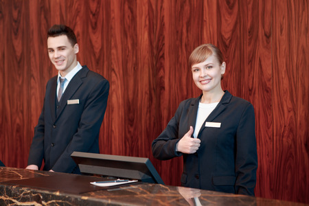 Photo for Only best hotel service. Good-looking female receptionist in selective focus shows her thumb up and male receptionist welcomes guest smiling friendly - Royalty Free Image