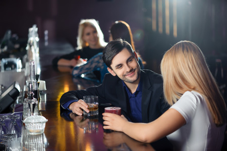 Photo pour Long night. Couple joyfully interacting by the bar counter in nightclub or restaurant - image libre de droit