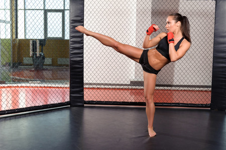 High kick. Strong sportswoman shows her high kick in a boxing ring