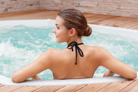 Photo pour Beautiful spa. Back view of a young woman enjoying Jacuzzi in a spa center - image libre de droit