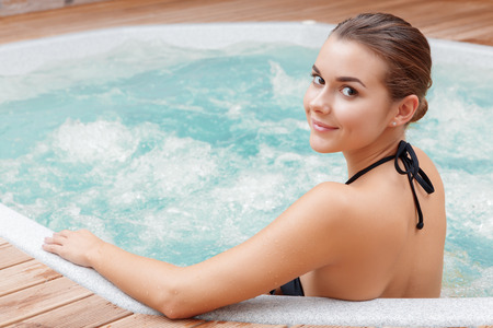 Photo for Beautiful spa. Back view of a young woman enjoying Jacuzzi in a spa center - Royalty Free Image