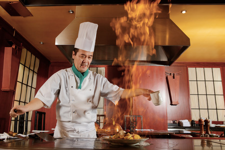 Kitchen hell. Japanese cook frying a vegetarian meal in burning flame of spirit on restaurant kitchen