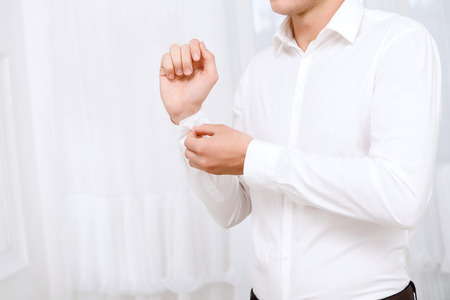 Foto de Last step. Close up of man buttoning up sleeve of white shirt on background of white curtains. - Imagen libre de derechos