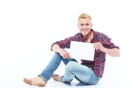 Center of attention. Handsome young man sitting on floor with white sheet of paper on isolated white background.